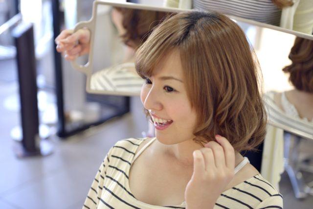 切った髪の毛を確認する女性